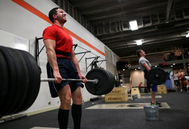 Two men work out at a gym/CrossFit class.
