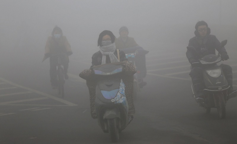 Chinese commuters ride through polluted air