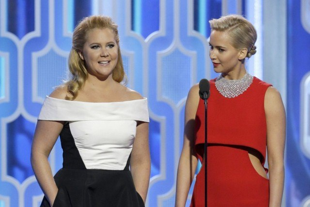 Jennifer Lawrence stands with Amy Schumer on stage while speaking at an awards ceremony.