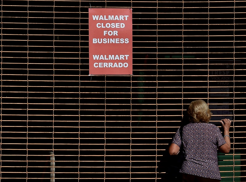 A woman peers into a closed Walmart