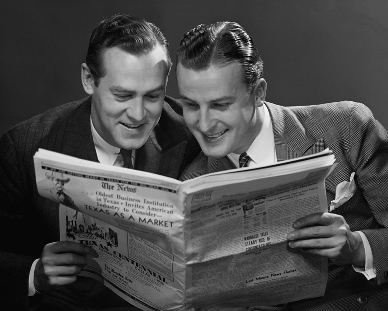 Two men reading a newspaper together, as if that's normal