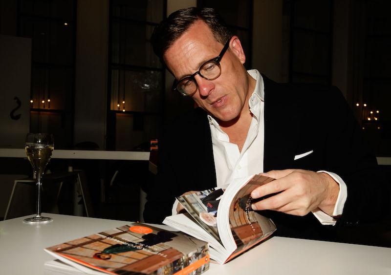 a man looking through fashion books