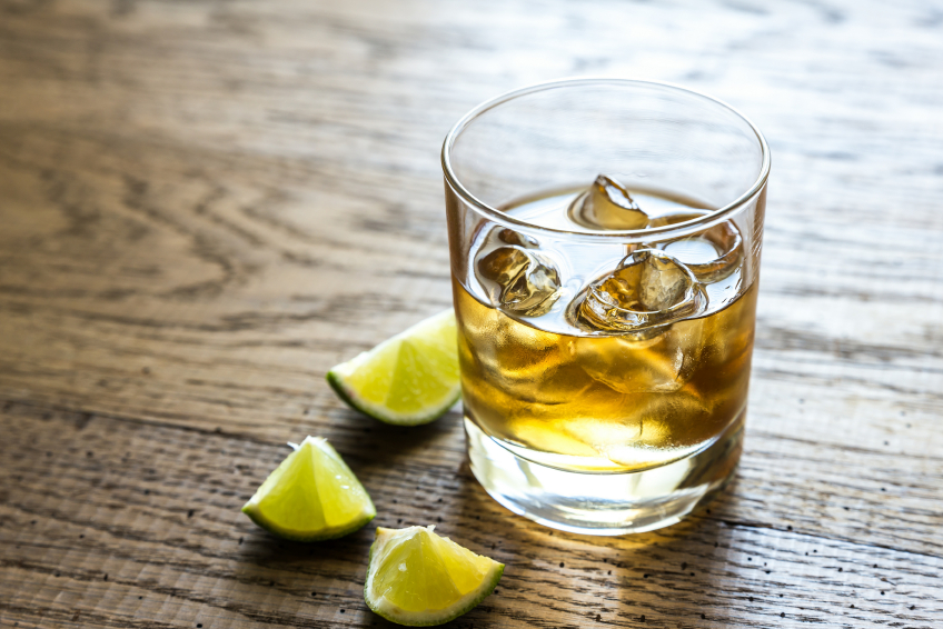 rum cocktail with ice and limes on a wooden table