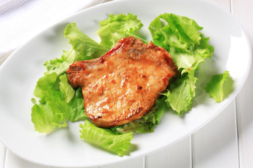 glazed pork chop on lettuce leaves over a white platter