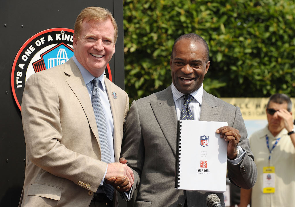NFL Commissioner Roger Goodell and NFLPA Executive Director DeMaurice Smith celebrate the signing of the league's new collective bargaining agreement.