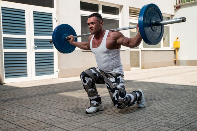 mean wearing camo pants performing barbell unges outside on the cement