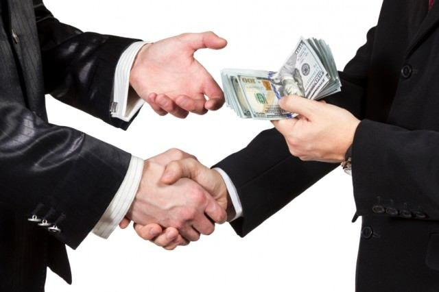 Men exchanging money and shaking hands