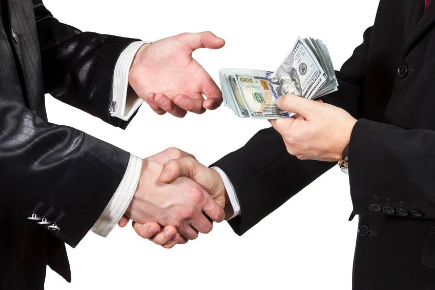 Two men shaking hands and exchanging money