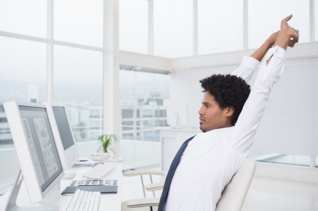 man stretches at his desk