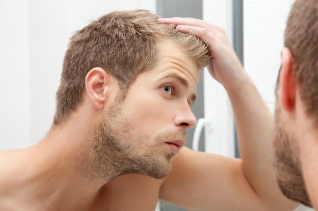 Man examining his hair in the mirror