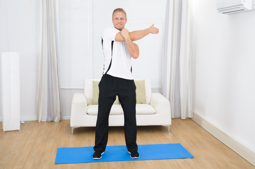 cheerful man doing exercise on mat