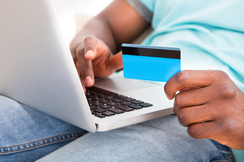 Young man using credit card on laptop