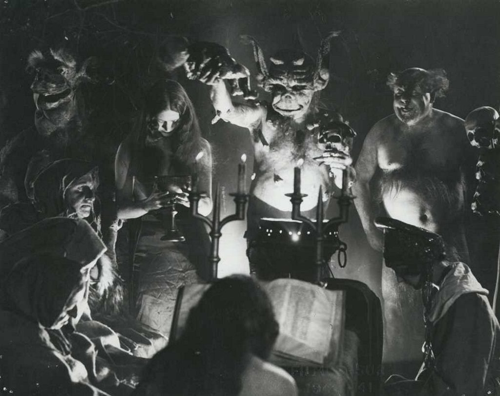 A scene from the movie Häxan where demons are standing around lit candles and a large text while human women bow their heads