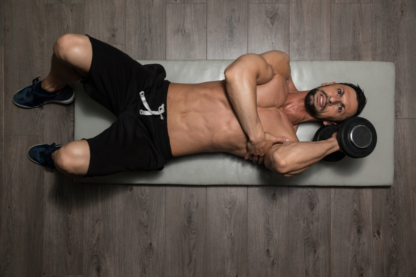 man lying on an exercise mat lifting a dumbbell with one hand