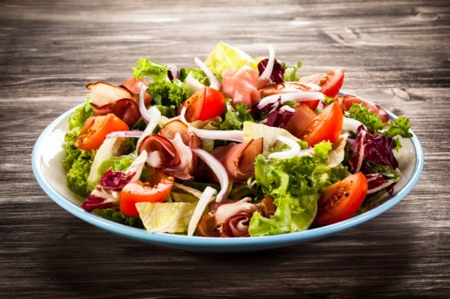 A salad with vegetables in a blue and white bowl.