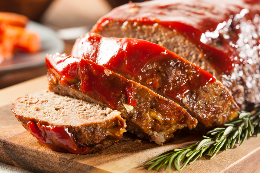 sliced meatloaf with ketchup glaze on a cutting board