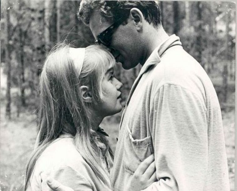 A young woman wearing a headband with her hands on the chest of a man in sunglasses in the woods in I Am Curious (Yellow)