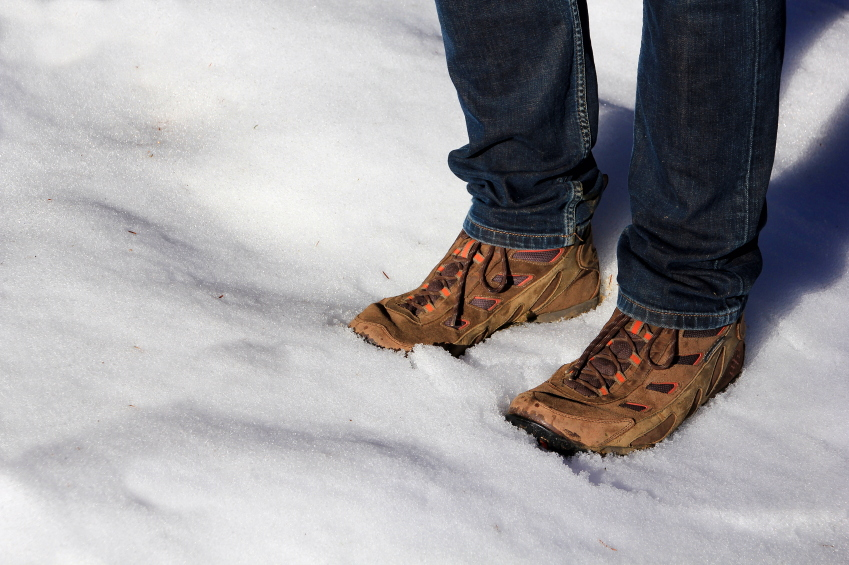 man wearing snow boots in the snow