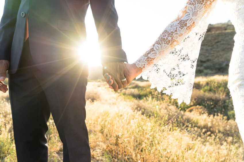married couple holds hands in a field