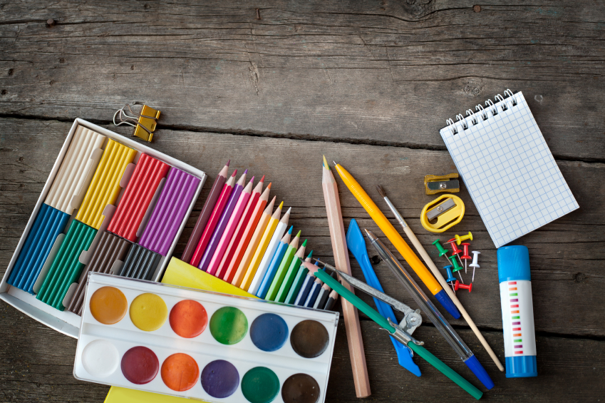 colored pencils, paints, notebook set out on a table for crafts