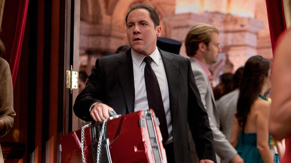Jon Favreau as Happy Hogan in a suit carrying a red case