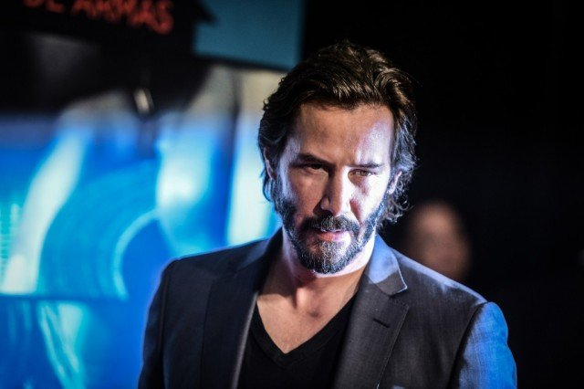 Keanu Reeves standing in a gray blazer as he looks forward and downward while attending a movie premiere.