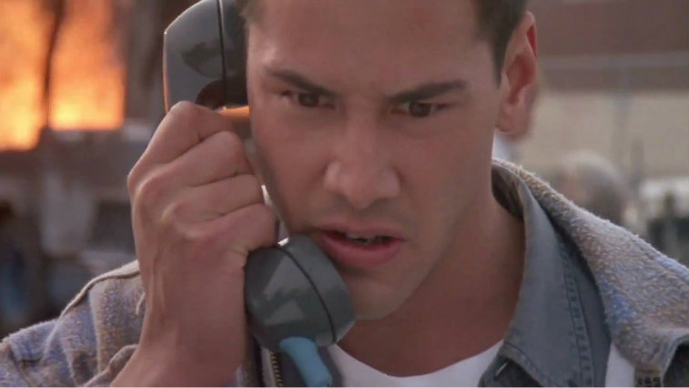 Keanu Reeves is looking angry as he is talking on a pay phone.