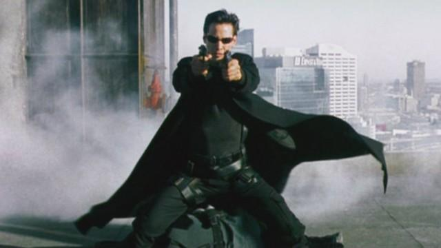 Keanu Reeves is on a rooftop and is holding up two guns in The Matrix.