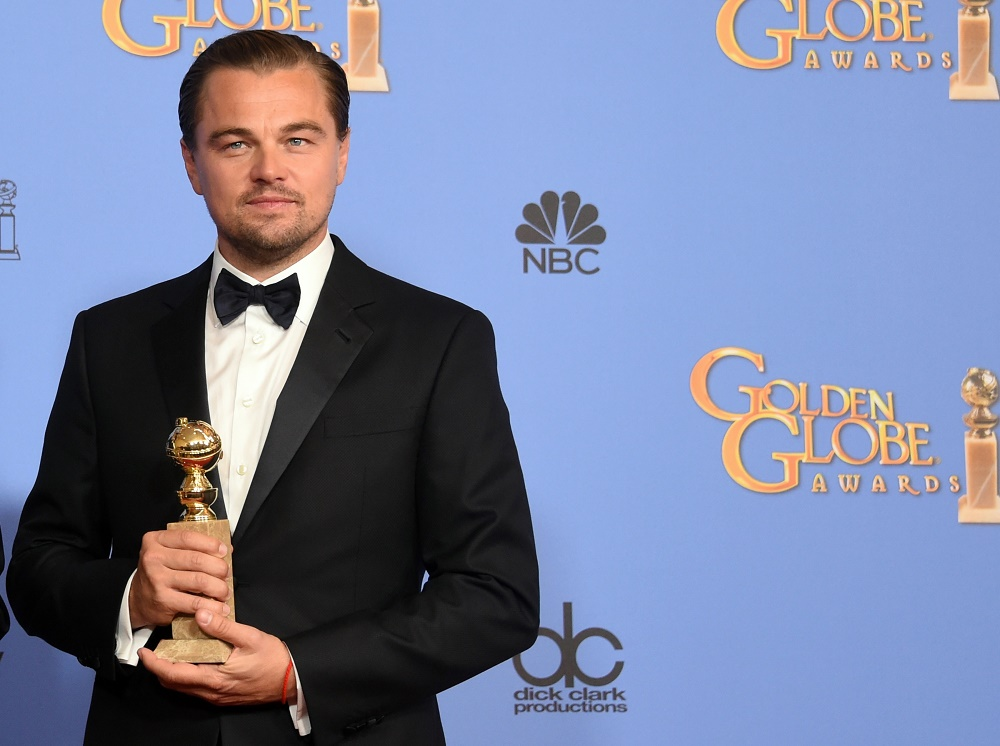 Leonardo DiCaprio is at the Golden Globes holding his award.