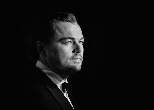 Leonardo DiCaprio stands in a black suit in front of a black background.