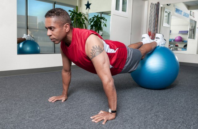 man doing push-ups with a stability ball at the gym