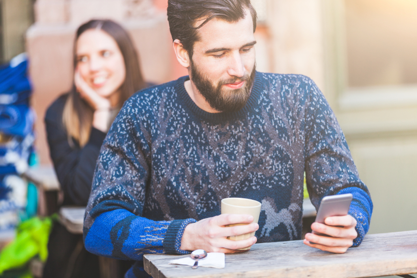 man using smartphone in a cafe