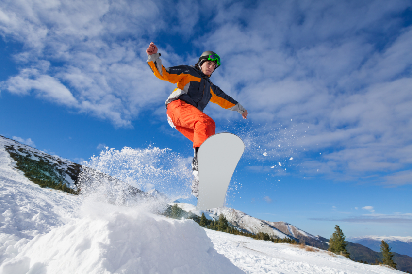 man going off a jump on a snowboard