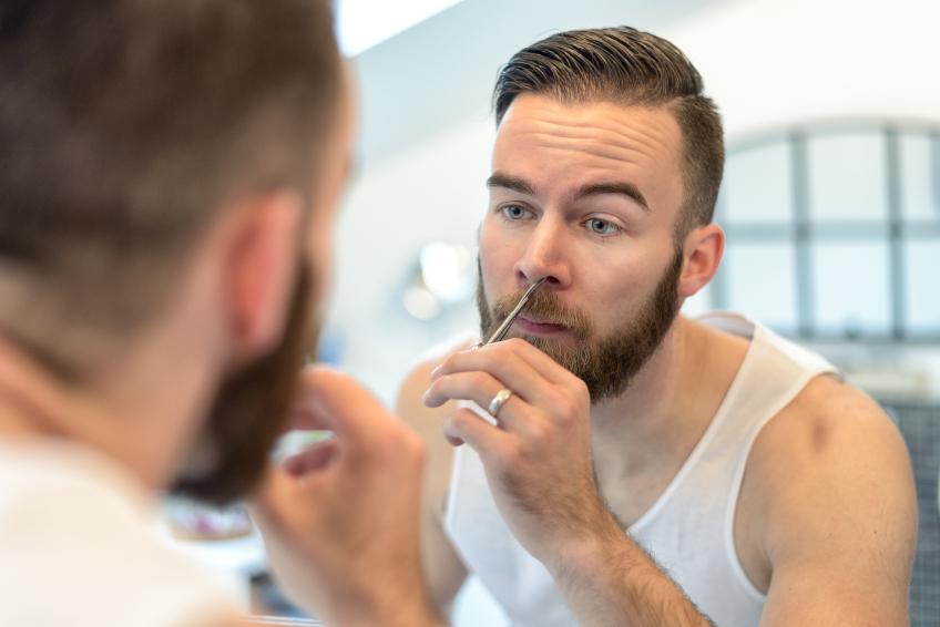 man plucking his nasal hairs