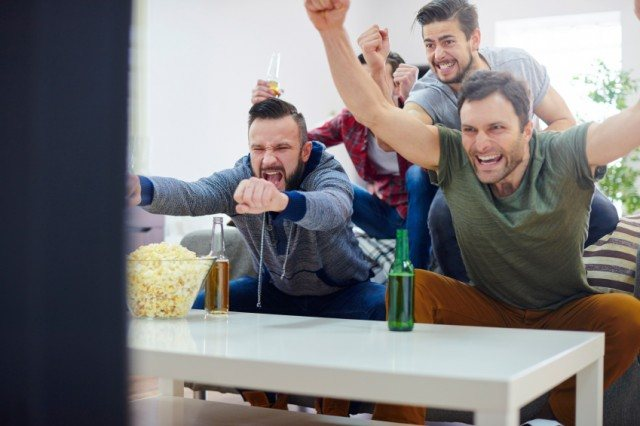 men cheering together in front of the TV