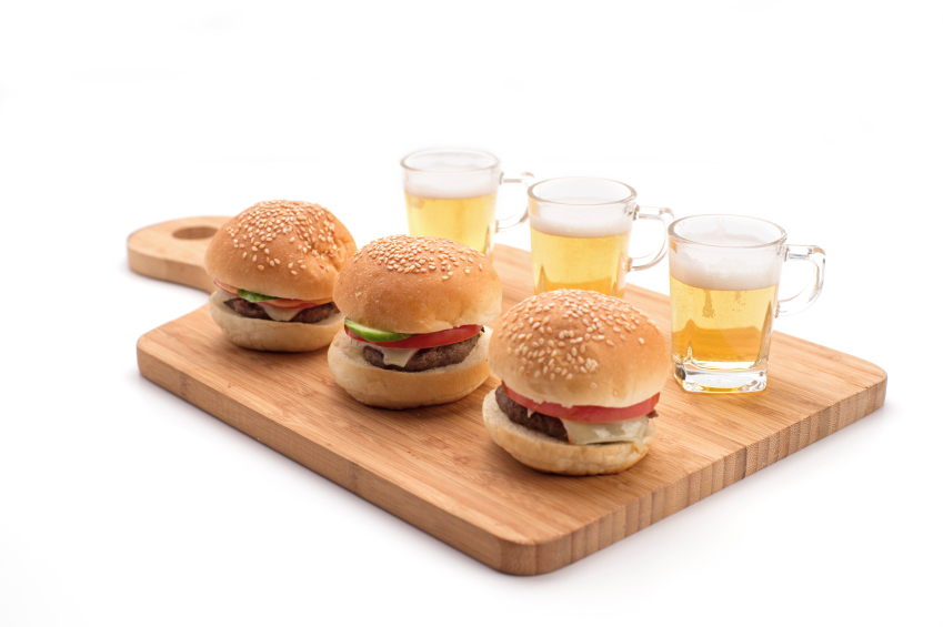 three burgers and beers on wooden board
