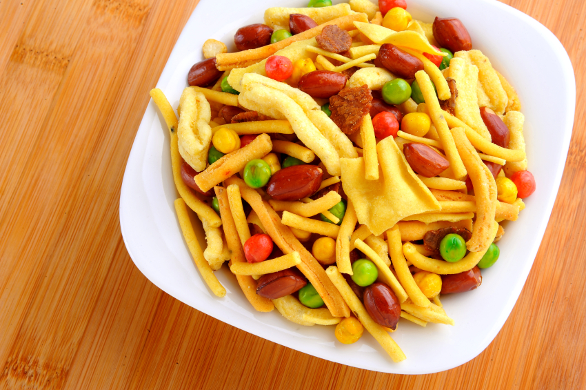 snack mix with peas, peanuts, and cheese straws in a white dish set on a wooden table
