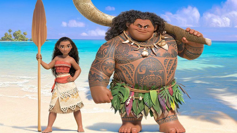 Moana and Maui stand next to each other on a beach.