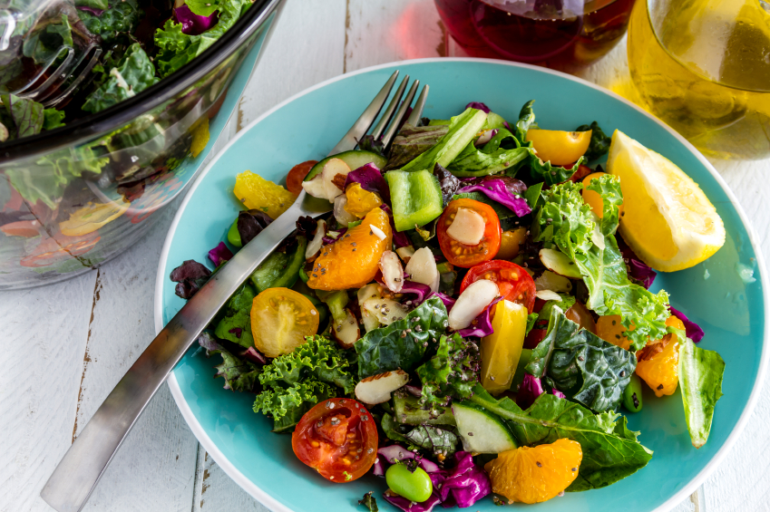 fresh salad with kale, tomatoes, and oranges in a blue bowl