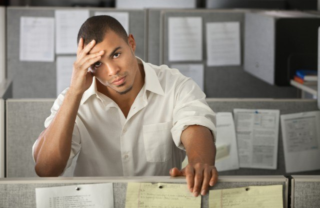 Man holding his head at work