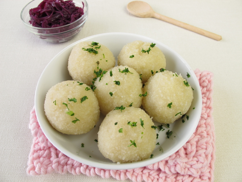 bowl of potato dumplings with parsley and a side of braised red cabbage