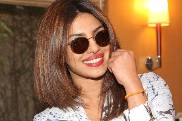 Priyanka Chopra smiling while wearing sunglasses.