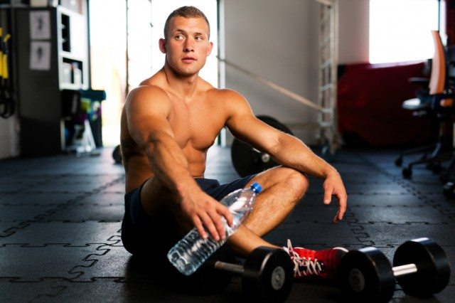 Man sitting on the gym floor with a water bottle