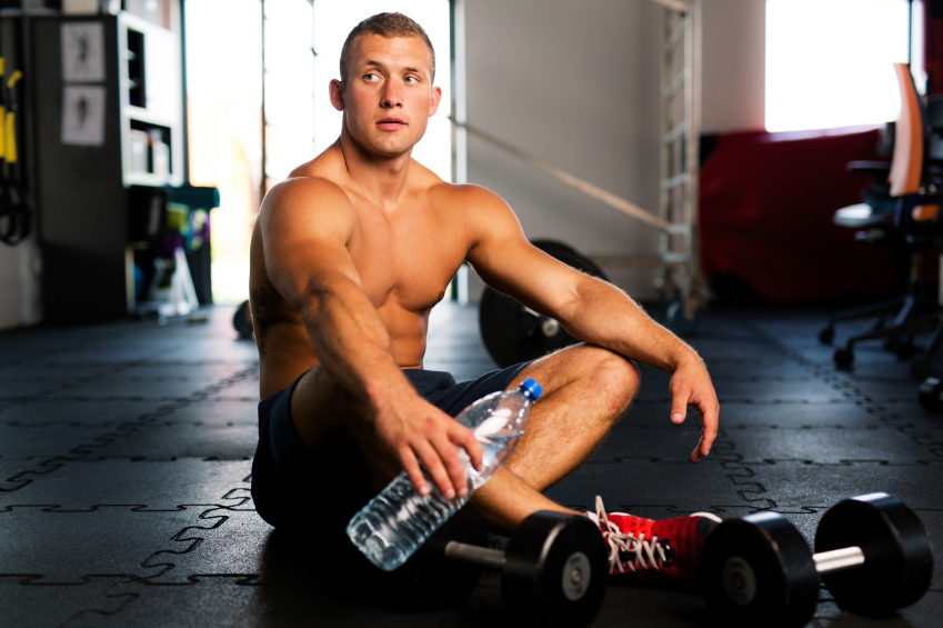 Young muscular man resting and drinking water after workout