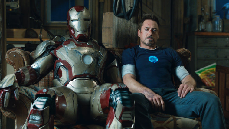 Robert Downey Jr. sits next to his Iron Man suit in Iron Man 3