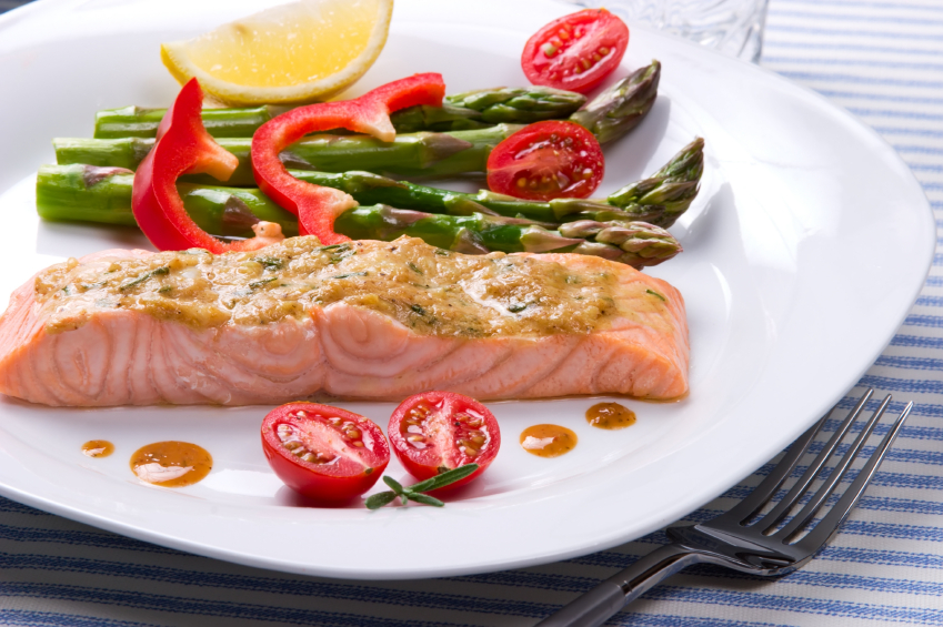 salon with a mustard and herb topping served with peppers, tomatoes, and asparagus