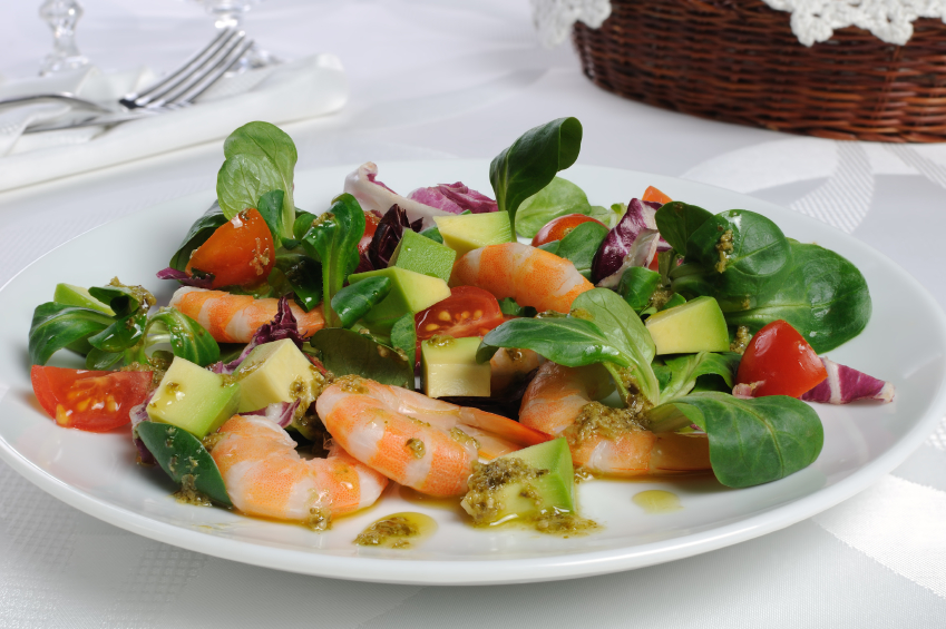 elegant table with a salad of shrimp, avocado, watercress, and tomato
