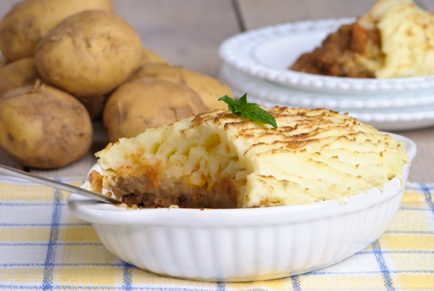 white casserole dish filled with shepherd's pie being scooped out
