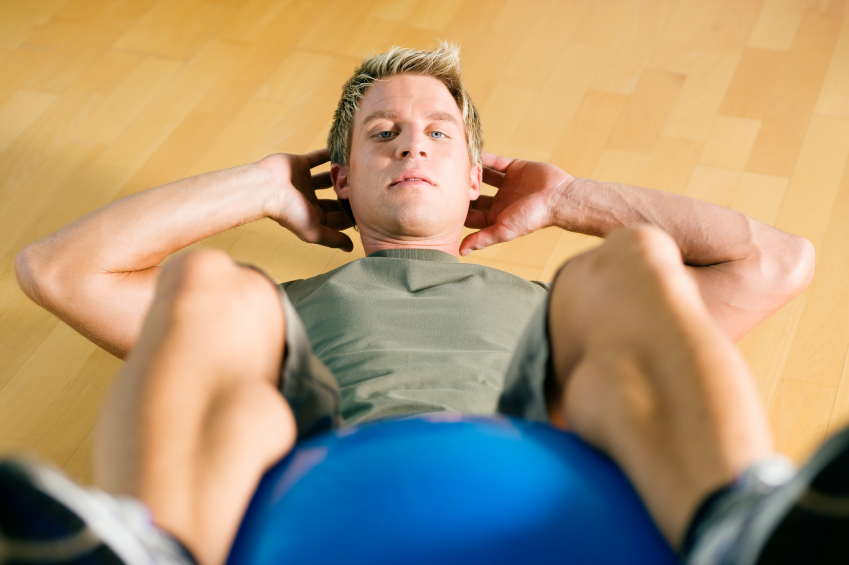 Man doing sit-ups on fitness ball
