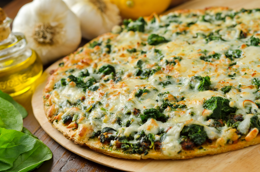 thin-crust spinach pizza ready to be sliced